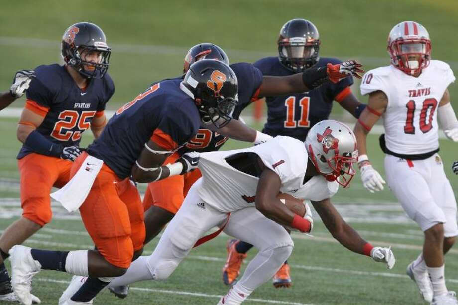 Travis' Nick Harvey is brought down by Seven Lakes' Bright Ugwoegbu during the Spartans' 31-14 victory Sept. 12 at Rhodes Stadium. To view or purchase this photo and others like it, go to HCNPics.com. Photo: Alan Warren