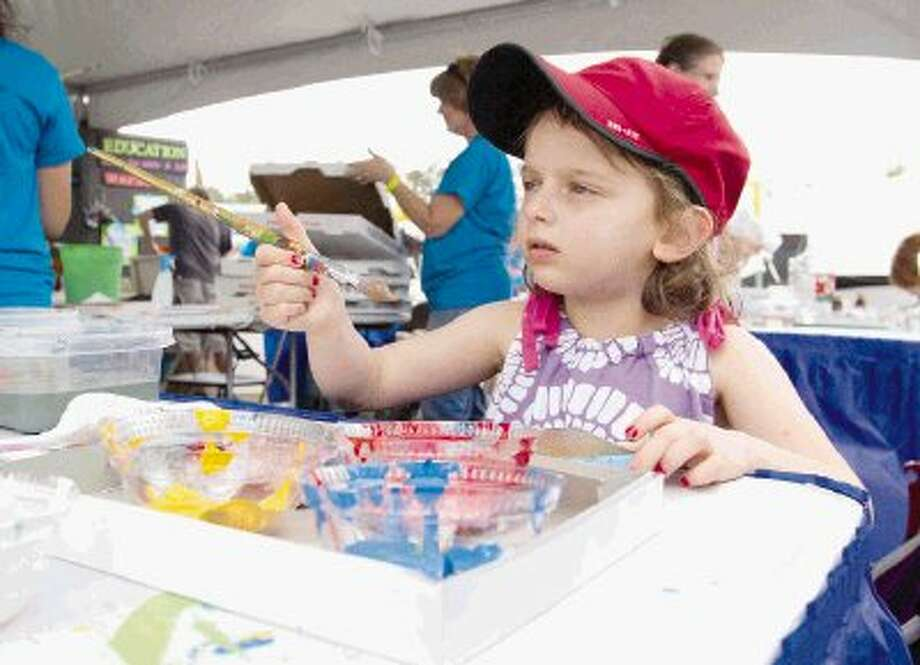 Noa Shaw paints a box during The Woodlands Waterway Arts Festival. Thousands enjoyed music, art and crafts during the festival. To view or purchase this photo and others like it, visit HCNpics.com. Photo: Jason Fochtman / Conroe Courier / HCN