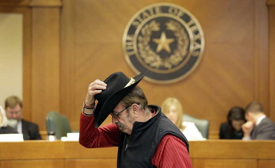 Jerry Williams replaces his hat after giving testimony at a hearing in which lawmakers discuss whether to legalize concealed handguns on college campuses and open carry everywhere Thursday in Austin. Photo: Eric Gay