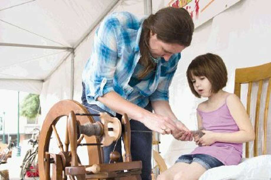Hannah Hrivnatz teaches 6-year-old Marian Fuqua how to spin wool from shetland sheep during Conroe KidzFest 2014 in downtown Conroe Saturday. Youths and their parents enjoyed playing games, jumping on inflatables and watching live performances. An estimate of 15,000 to 20,0000 people came through the gates for this year's event. To view or purchase this photo and others like it, visit HCNpics.com. Photo: Staff Photo By Ana Ramirez / The Conroe Courier