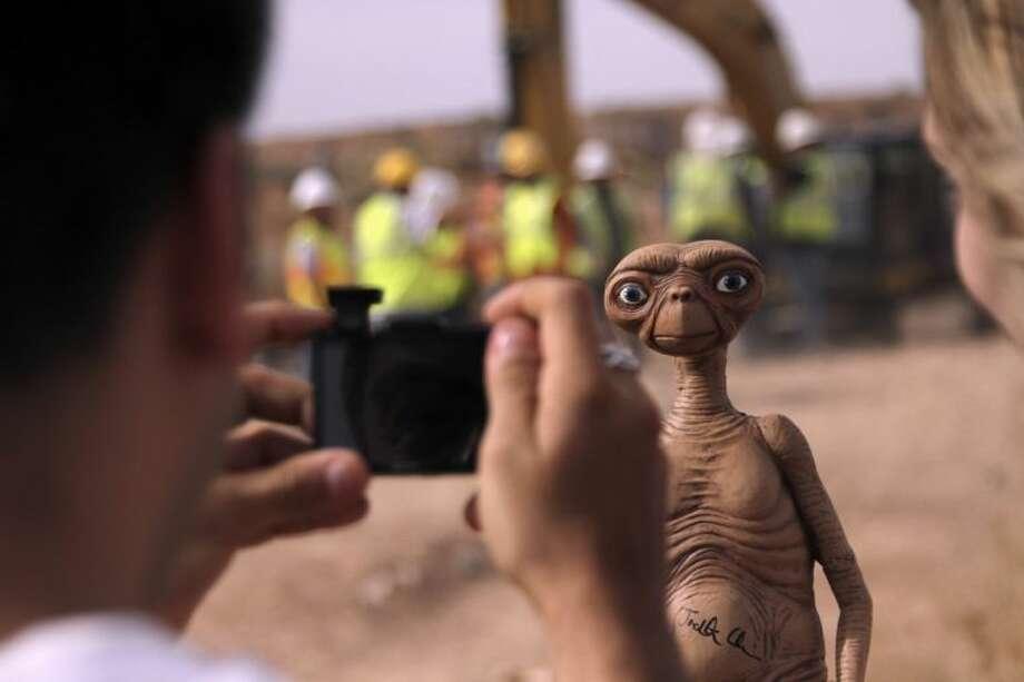 A man takes a photo of an E.T. doll in Alamogordo, N.M, Saturday.