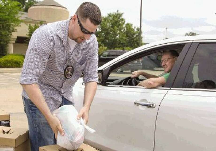 Gerrit Wolfhagen, a task force officer with the Drug Enforcement Administration, collects a bag of unused prescription medication brought by Donnie Nichols during National Prescription Drug Take Back Day at the Conroe Police Department Saturday. The program was designed to help prevent prescription drug abuse. / Conroe Courier
