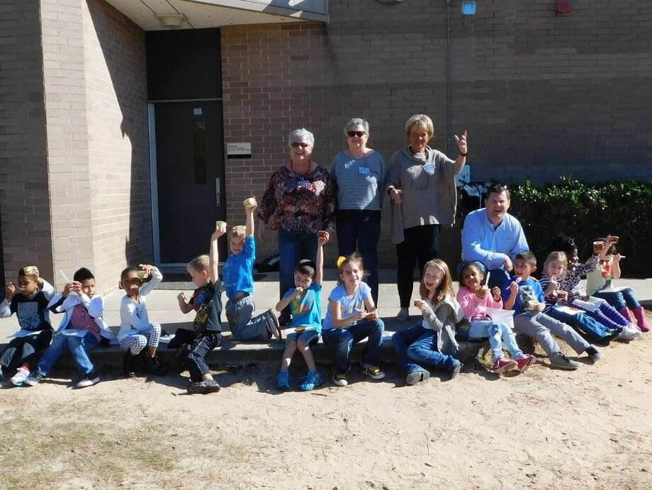 Conroe Noon Lions Club members recently hosted 'Bee Club' at their adopted school of Reaves Elementary by handing out ice cream treats. Members pictured in back from left to right: Nancy Edgmon, Sandy Apostolo, Inge Merle, and Bobby Brennan.