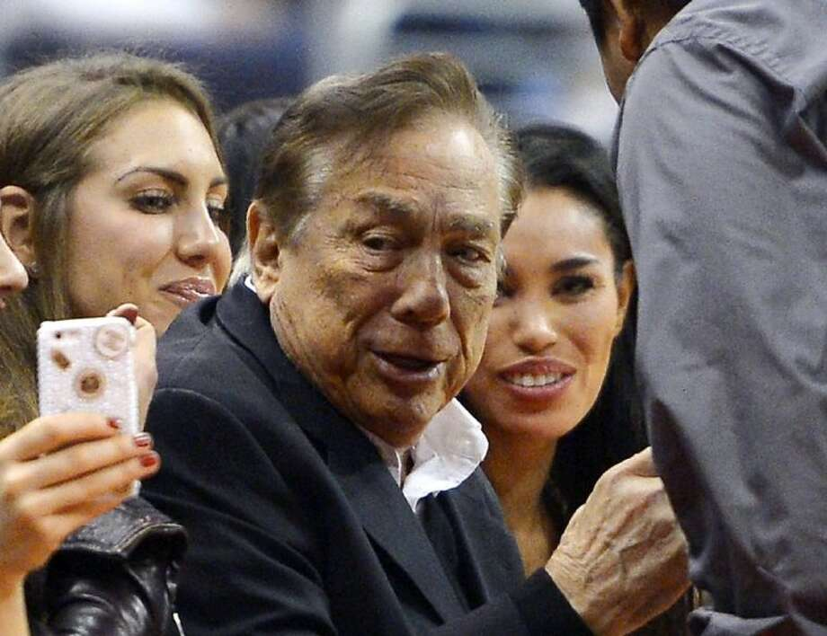 In this photo taken Oct. 25, 2013, Los Angeles Clippers owner Donald Sterling, center, and V. Stiviano, right, watch the Clippers play the Sacramento Kings during the first half of an NBA basketball game in Los Angeles.