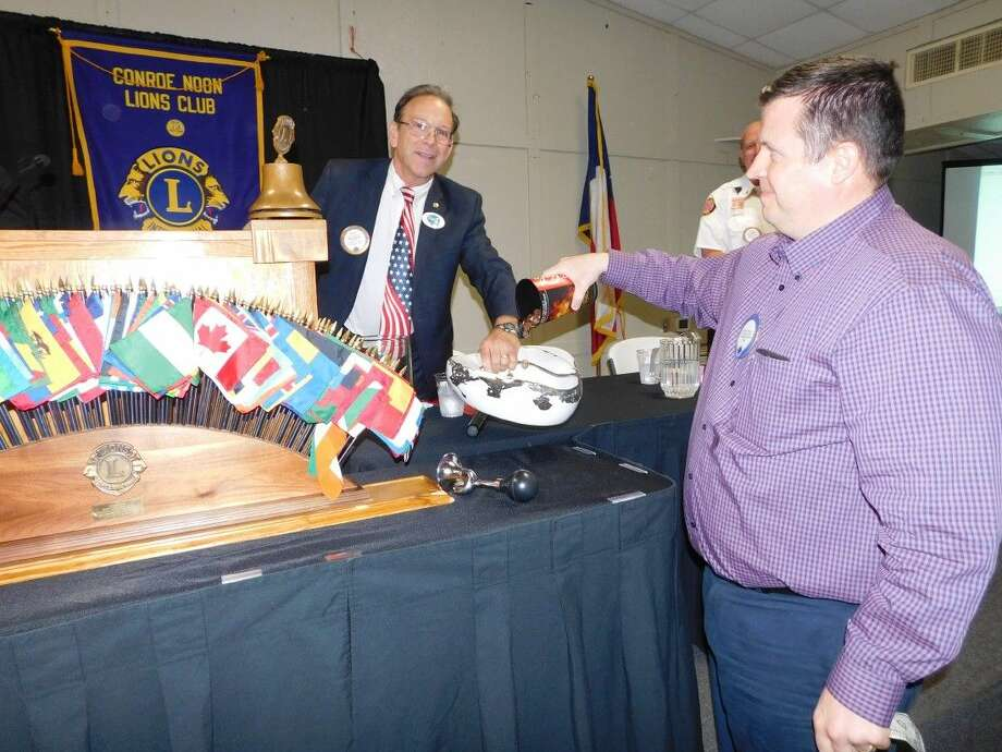 Last week Conroe Noon Lions Club President Karl Johnson, left, 'fined the finer'; after which Tail Twister Warner Phelps, right, graciously paid his fine by dumping $10 worth of pennies into the pot.