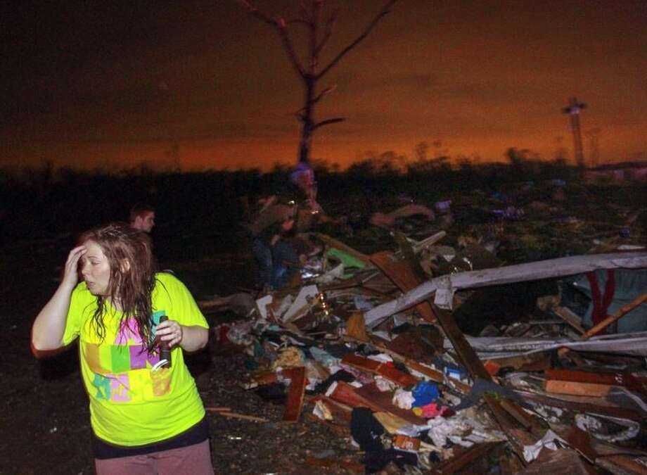 In this Sunday photo, Lauren Watts searches for her dog in Mayflower, Ark., after a tornado struck the town. A tornado system ripped through several states in the central U.S. and left more than a dozen dead in a violent start to this year's storm season, officials said. Photo: Benjamin Krain
