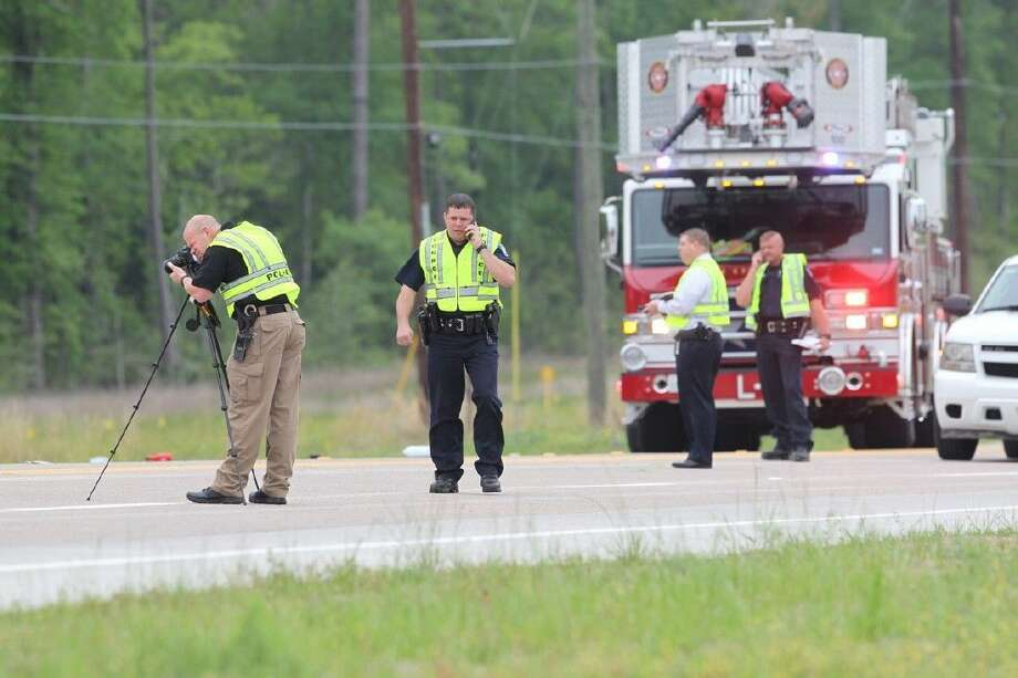 Investigators with Conroe Police Department survey the scene of a fatal crash this morning on South Loop 336 West.