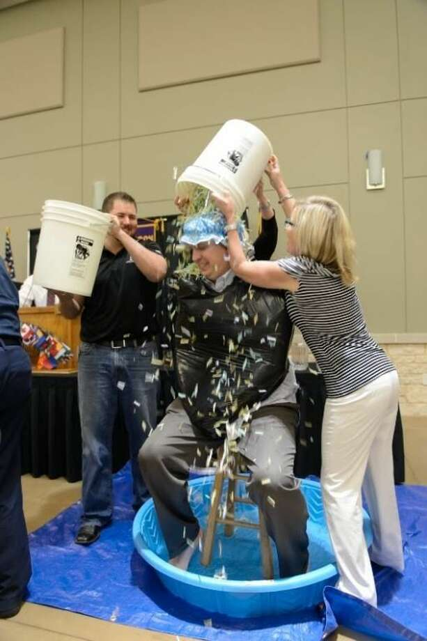 Lucky for Conroe Noon Lions Club board member Warner Phelps, center, the April Fool's joke was on him as Membership Committee members Ryan Morton, left, and Mona Hamby dowse him with a bucket of confetti, rather than the bucket filled with ice water.