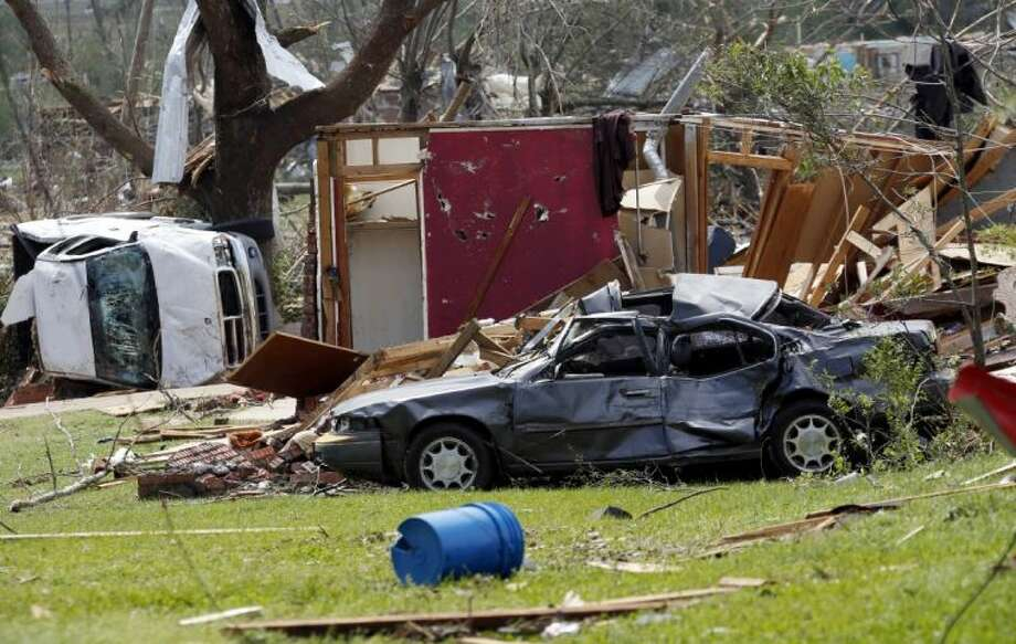 Destroyed automobiles and remnants of homes cover the ground in a south Louisville, Miss., neighborhood, Tuesday. A dangerous storm system that spawned a chain of deadly tornadoes over two days flattened homes and businesses, and killed dozens from the Midwest to the Deep South.