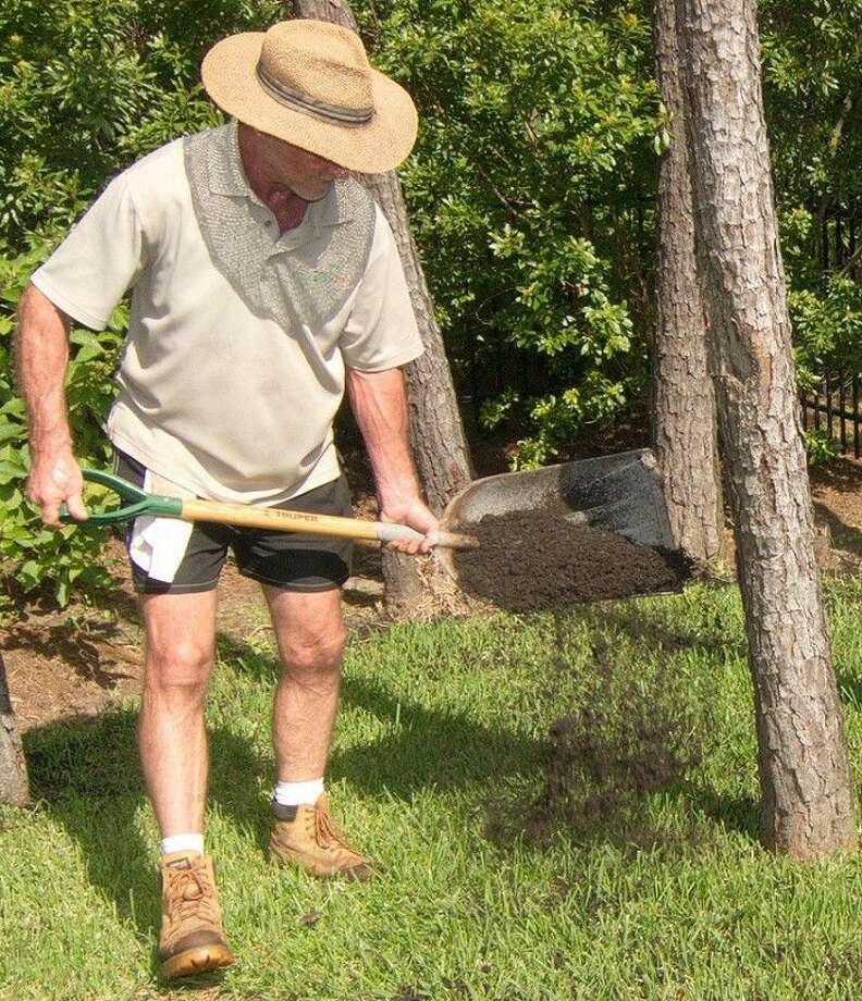 Lawn care expert Jim Faulk spreads compost.