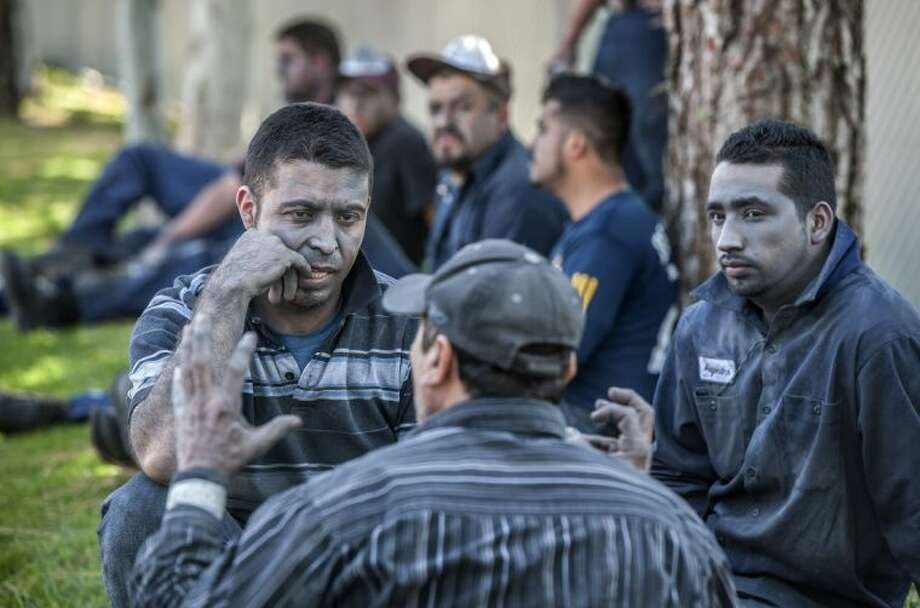 Workers from a chrome finishing company sit outside talking after an explosion in La Habra, Calif., Tuesday.