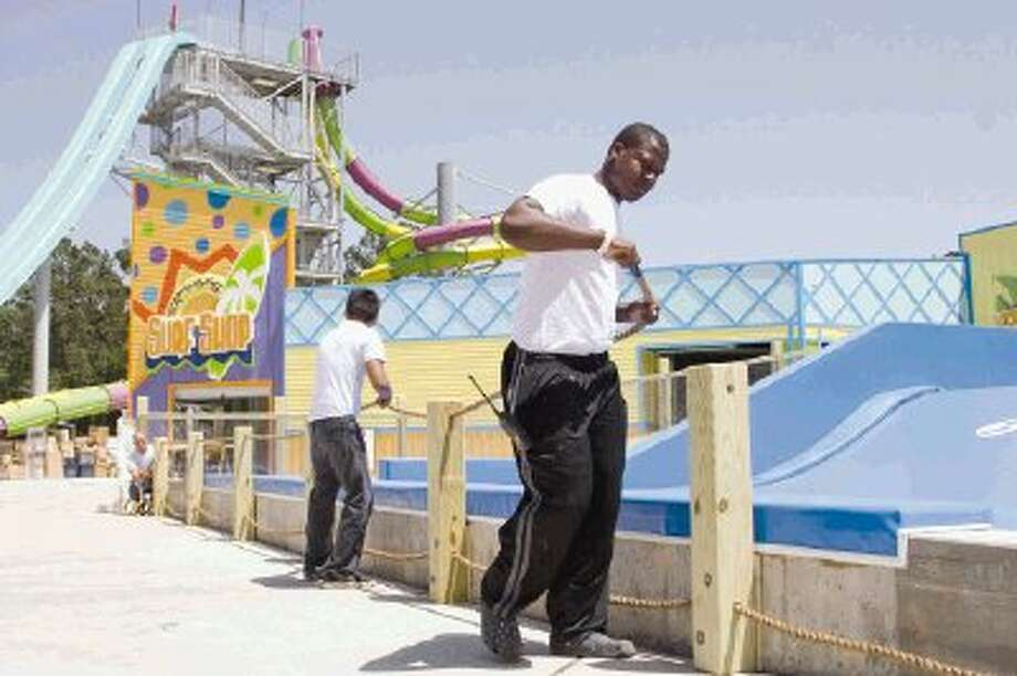 Maintenance workers add ropes along the FlowRider, one of the three new additions at Wet 'n' Wild SplashTown, in Spring April 28. The water park recently went through a multi-million dollar makeover and was unveiled to the public May 2. / The Conroe Courier