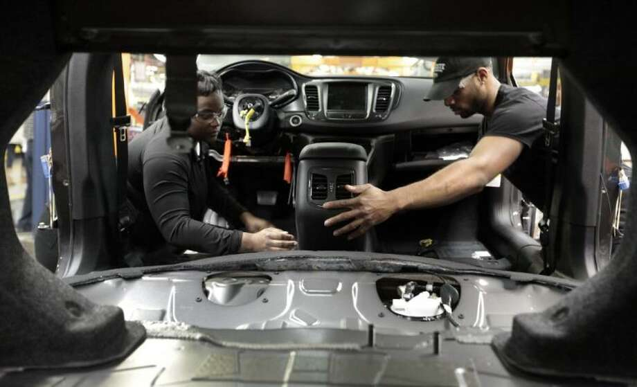 In this March 14, 2014 photo, assembly line workers build a 2015 Chrysler 200 automobile at the Sterling Heights Assembly Plant in Sterling Heights, Mich. Photo: Paul Sancya