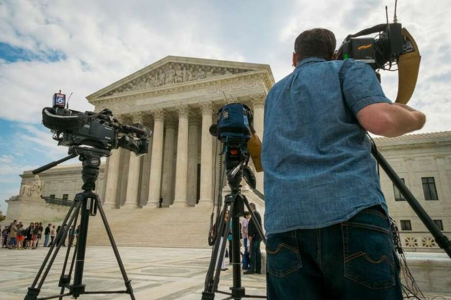 This April 22, 2014 file photo shows videojournalists setting up outside the Supreme Court in Washington. The court said Monday it will hear the case of a Florida fisherman who wants the court to throw out his conviction for getting rid of some small grouper under a federal law originally aimed at the accounting industry. Commercial fishing boat captain John Yates argues that the federal government used its mighty power to convict him of tossing overboard three fish that were under the 20-inch minimum legal size for red grouper caught in the Gulf of Mexico. Photo: J. David Ake
