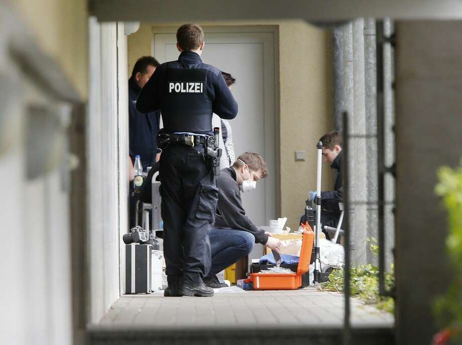 German police officers secure evidence in front of an apartment on Thursday in Oberursel, Germany. Photo: Michael Probst