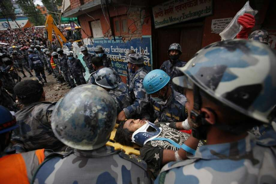 Pemba Tamang is carried on a stretcher after being rescued by Nepalese policemen and U.S. rescue workers. Crowds cheered Thursday as Tamang was pulled, dazed and dusty, from the wreckage of a seven-story Kathmandu building that collapsed around him five days ago when an enormous earthquake shook Nepal. Photo: Niranjan Shrestha