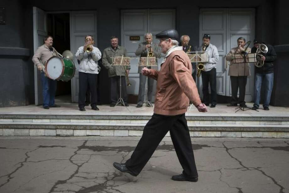 An elderly man marches in front of an amateur band while local citizens gather to mark May Day in Slovyansk, eastern Ukraine, Thursday, May 1, 2014. Russian state news media were quick to dismiss the protests as the work of Ukrainian neo-Nazis, a particularly loaded accusation because Ukrainian nationalists collaborating with the Nazis are blamed for horrific reprisal attacks during World War II.