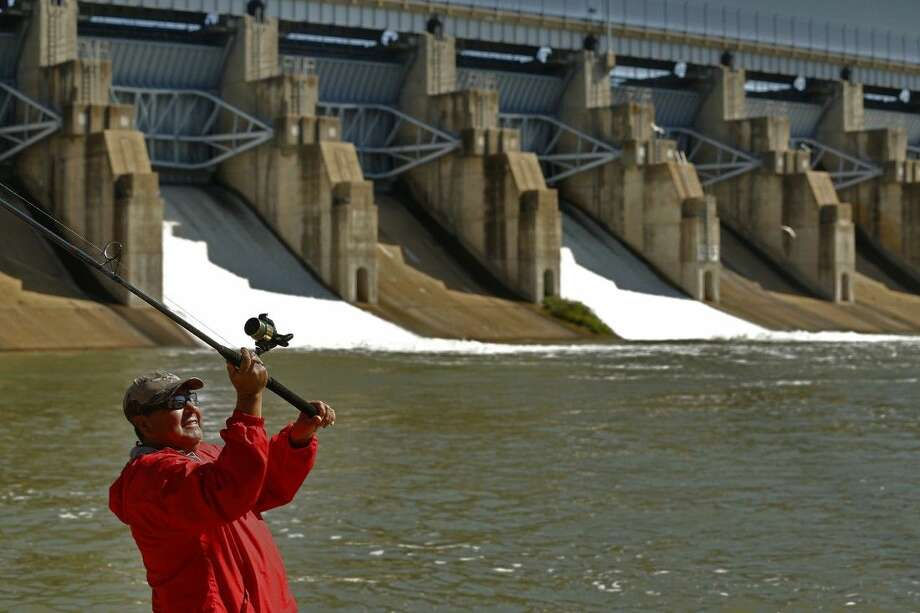 Antonio Pinon casts into the spillway of Lavon Lake after the Army Corps of Engineers opened up three doors in the dam on Wednesday. Photo: Nathan Hunsinger