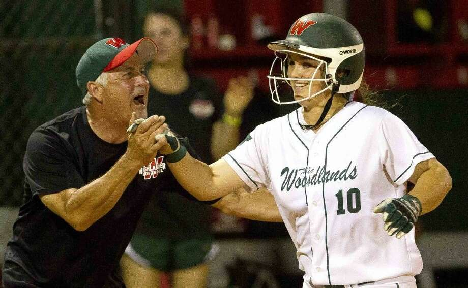 The Woodlands' Kelcy Leach celebrates with coach Richard Jorgensen after hitting a two-run home run in the sixth inning of a bi-district softball game Friday. To view or purchase this photo and others like it, visit HCNpics.com. Photo: Jason Fochtman