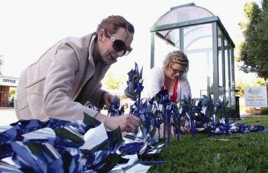 Clare Lucas and Michelle Sanson place blue pinwheels in the ground near the Alan B. Sadler Administration building in downtown Conroe. More than 1,000 pinwheels were placed in recognition of Child Abuse Awareness Month.