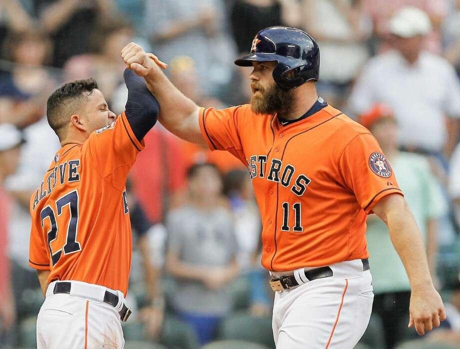 Houston Astros' Evan Gattis receives a high-five from Jose Altuve, left, after hitting a home run Friday in Houston. Photo: Bob Levey