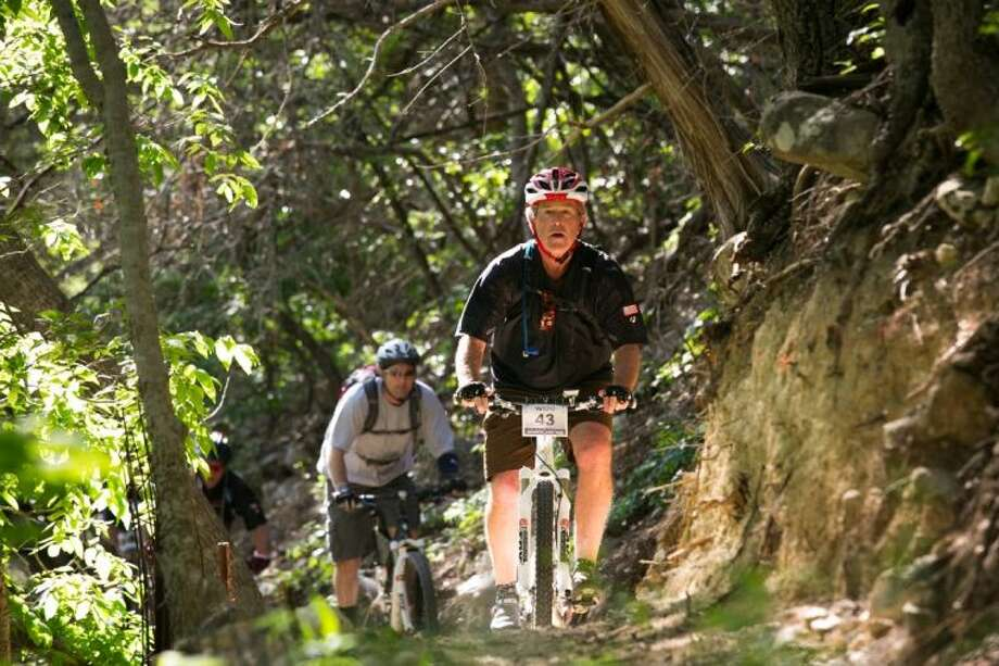 Former President George W. Bush leads the second day of a three-day, 100-kilometer mountain bike ride with 16 wounded veterans Friday in Crawford.