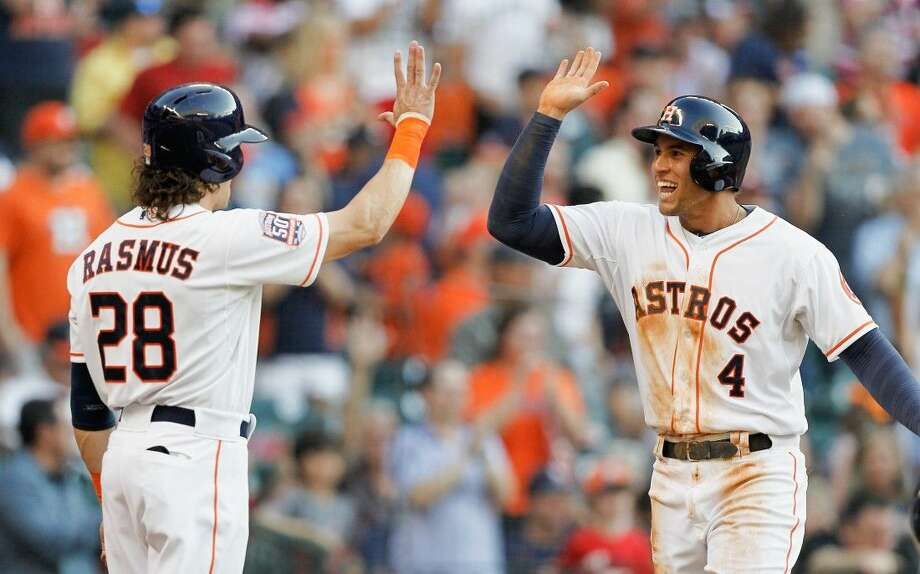 Houston Astros' George Springer receives a high five from Colby Rasmus after scoring on a home run by Evan Gattis on Saturday in Houston. Photo: Bob Levey