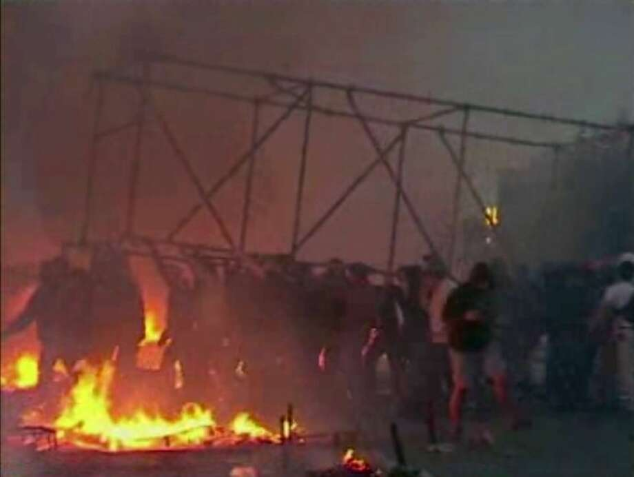 This image made from AP video shows people carrying a scaffolding frame through fires on the ground in Odessa, Ukraine, on Friday.