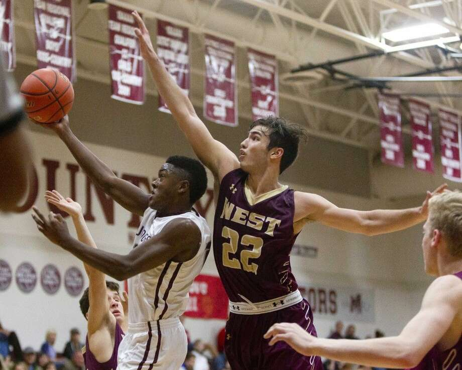 Magnolia guard Michael Woods goes up for a shot as Magnolia West power forward Colin Just defends during the fourth quarter of a District 19-5A basketball game this past season. To purchase this photo and others like it, go to HCNpics.com. Photo: Jason Fochtman