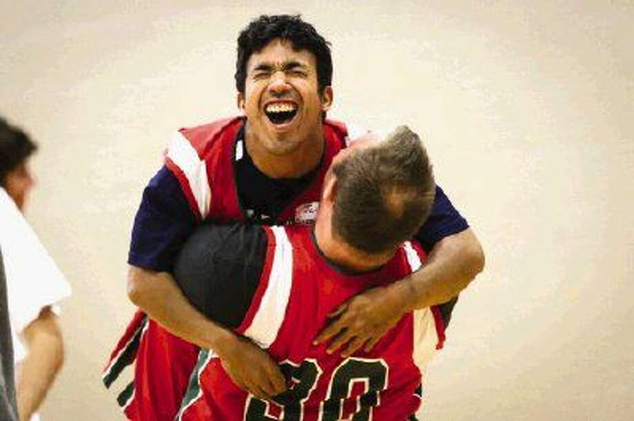 John Sisson, 24, left, hugs Seth Jenkins, 19, right, after scoring a basket during the eighth annual Challenger Camp Rebound Saturday at The Woodlands High School Ninth Grade Campus. Camp attendees could play and learn basketball with members of The Woodlands basketball teams and coaches.