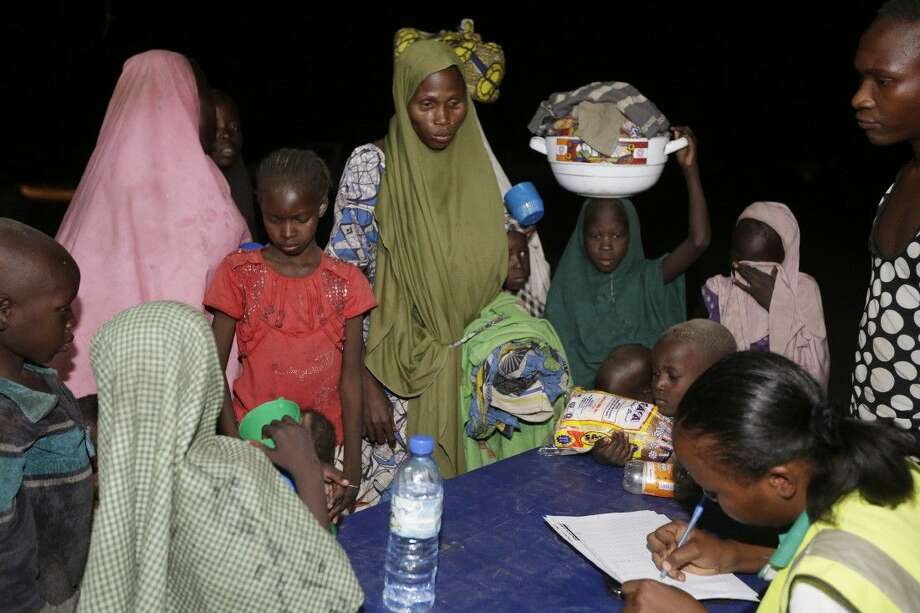 Women and children who were rescued by Nigerian soldiers from Boko Haram extremists at Sambisa Forest register their names upon their arrival at a refugee camp in Yola, Nigeria Saturday. Photo: Sunday Alamba