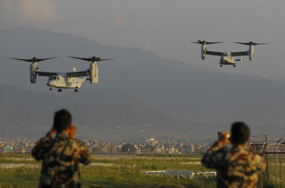 Nepalese soldiers take pictures as US Air Force Bell Boeing V-22 Osprey aircrafts arrive at the Tribhuvan International airport in Kathmandu, Nepal, Sunday. Runway damage forced Nepalese authorities to close the main airport Sunday to large aircraft delivering aid to millions of people following the massive earthquake, but U.N. officials said the overall logistics situation was improving. Photo: Niranjan Shrestha
