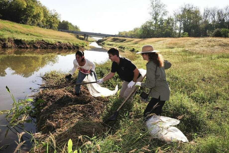 San Jacinto College faculty, staff, and students helped clean up portions of Greens Bayou, earning the College the Bayou Buddy award. Shown working together at a cleanup project are, from left, San Jacinto College student Maria Reyna, and science professors Stephan Lorenz and Susan Lustick.