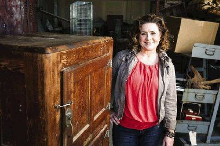 Artist Courtney Barge of Spring is re-purposing an antique ice box from Habitat for Humanity's ReStore facility as a wine cabinet that will be auctioned at the James Bond License to Build Gala in April. Photo: Michael Minasi