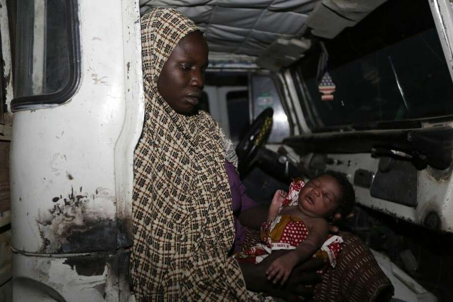 Lami Musa, abducted by Boko Haram five months ago from Lassa, holds her 4-day-old baby inside a truck after she arrived at a camp following her rescue by Nigeria soldiers from Islamist extremists at Sambisa Forest on Saturday. Photo: Sunday Alamba