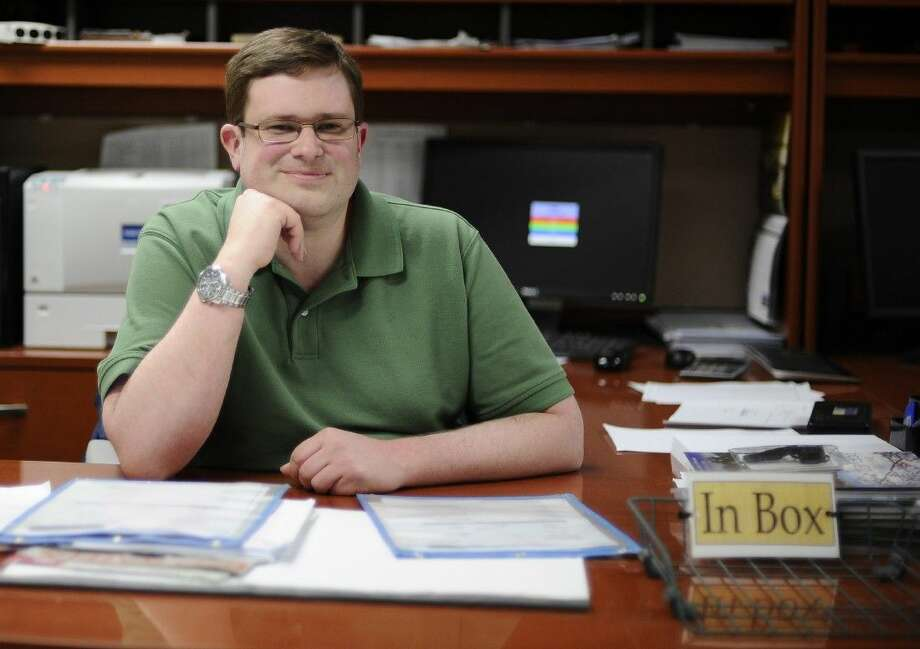 Bill Lewis at his desk at CMS Mailing in Monroe, Conn. Lewis was hired by CMS Mailing through Platform To Employment, a nonprofit program that offers to pay some long-term unemployed workers' salaries for their first eight weeks on a new job, essentially eliminating the companies' risk of hiring of them. Photo: Jessica Hill