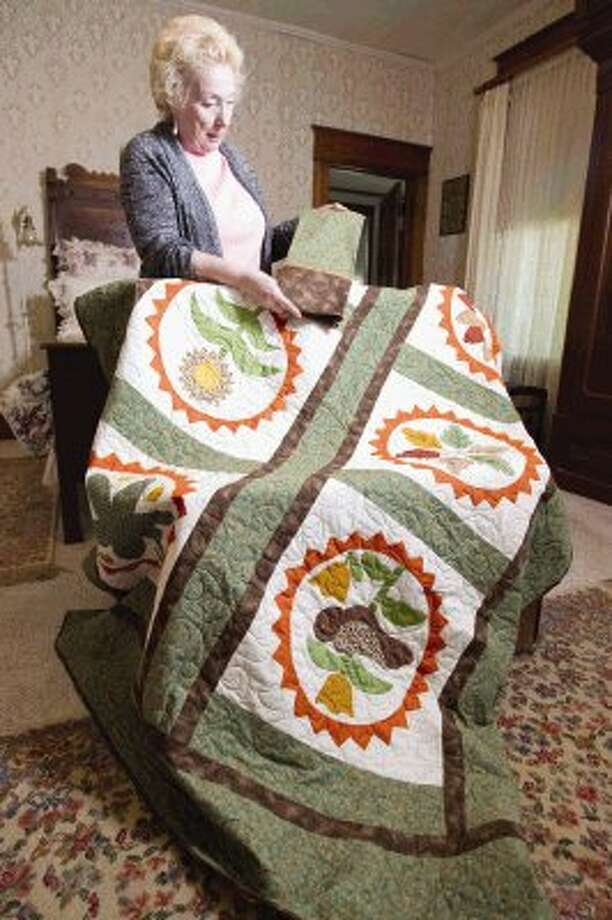 Sonya Clover, president of The Patrons of Cedar Brake Park, displays a quilt of squares by the late Anna Davis Weisinger in the 1960s. The quilt will be auctioned off May 15 as part of a fundraiser for the group. Photo: Jason Fochtman / Conroe Courier / HCN