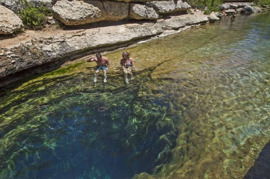 Art Larson, left, and Courtney Crockett sit on the edge of the Hays County's Jacob's Well Natural Area in Wimberley, Texas, on Wednesday, April 30, 2014. Photo: Rodolfo Gonzalez