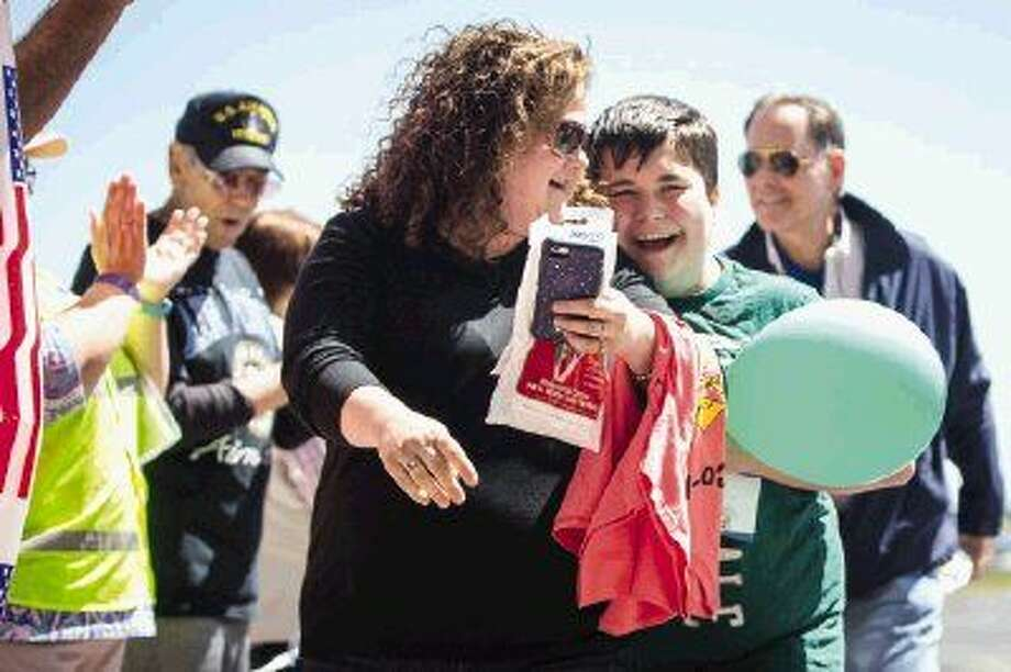 Conroe resident Angela Gilchriest walks her 13-year-old son Gabriel through an applauding crowd after Gabriel completed his flight during the Challenge Air event on Saturday at Conroe/North Houston Regional Airport. Photo: Michael Minasi