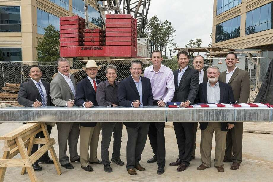 Signing a beam at the Topping Out of Three Hughes Landing and Embassy Suites The Woodlands/Hughes Landing are (from left to right): Kevin Viteri, general manager of the new Embassy Suites The Woodlands/Hughes Landing; Greg Parsons, vice president of Hospitality, The Woodlands Development Company; Peter Doyle, executive vice president, Strategic Development, The Howard Hughes Corporation; Mitch Gruberg, director of Building Development, The Woodlands Development Company; Eric Rabel, senior project manager, The Woodlands Development Company; Jim Carman, director of Building Development, The Howard Hughes Corporation; Michael Scheurich, president - general contractor, Arch-Con Corporation; Keith Carlson, president — architect of Mitchell Carlson Stone; John Stone, partner - architect, Mitchell Carlson Stone; and Travis Walla, senior project manager, The Woodlands Development Company.