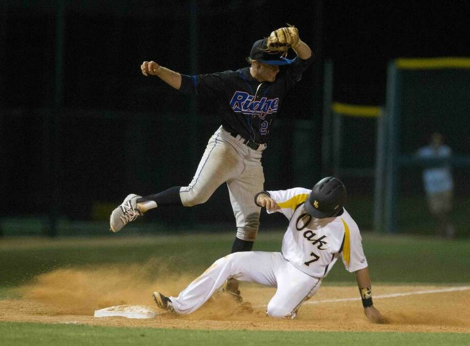 Oak Ridge third baseman Brock Woody tries to complete the tag of Klein Oak's Colin Durrett during a bi-district playoff game. Photo: Jason Fochtman