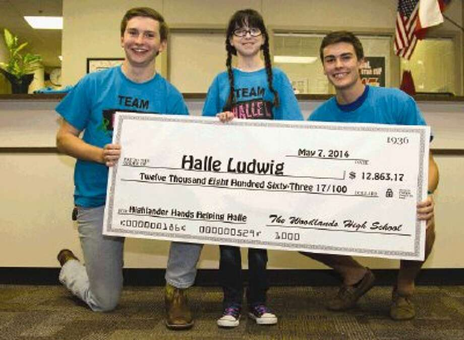 Halle Ludwig, a fifth-grader at Mitchell Intermediate, center, receives a check for almost $13,000 from Student Body President Chase Giles and Student Body Treasurer Jason Hulet at The Woodlands High School Thursday. Giles and Hulet, along with the student body, helped raise the money for Ludwig, who was born with autosomal recessive polycystic kidney disease and will be receiving her second kidney transplant. Photo: Staff Photo By Ana Ramirez / Conroe Courier
