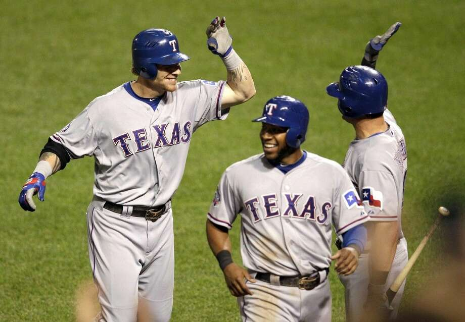 Texas Rangers' Josh Hamilton, left, high-fives Michael Young, right, after hitting his fourth home run of the game in a game against Balitmore in 2012. Photo: Patrick Semansky