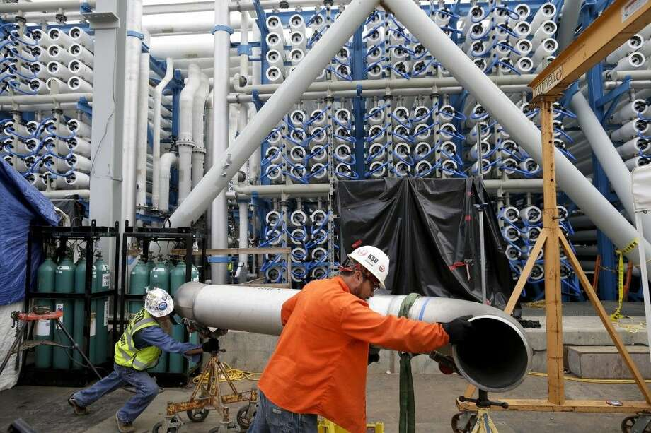Workers move a pipe in front of the 2,000 pressure vessels that will be used to convert seawater into fresh water through reverse osmosis in the western hemisphere's largest desalination plant in Carlsbad, Calif. Photo: Gregory Bull