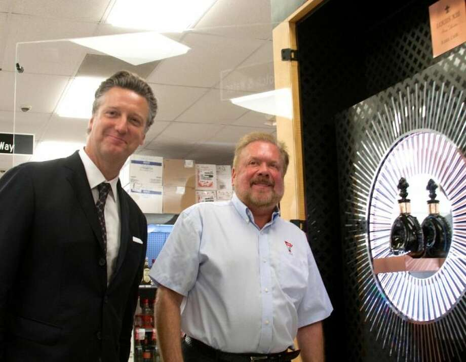Spec's CEO John Rydman (right) and Rémy Cointreau's vice president of Prestige Brands, Yves de Launay (left), in front of the Louis XIII Rare Cask 42,6 in its specially designed case at Spec's.