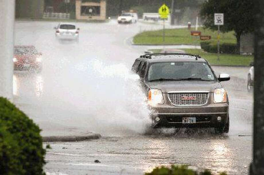 Traffic pushes through high waters Monday on Texas 105 and 149 in downtown Montgomery. The county experienced scattered thunderstorms throughout the day and is expected to receive rain for the rest of the week. Photo: Michael Minasi