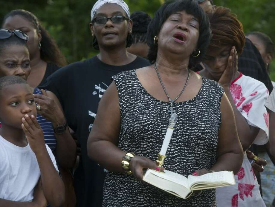 Hazel Embra holds a Bible while singing with others during a vigil for 93-year-old Pearlie Golden at Golden's home, Wednesday in Hearne. Golden was shot and killed outside her home by a Hearne police officer on Tuesday after she allegedly brandished a firearm, the Hearne Police Department said.