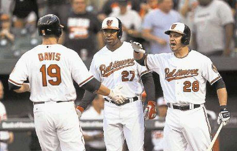 Orioles players Chris Davis, Delmon Young and Steve Pearce, right, wear uniforms with 'Baltimore' emblazoned on their jerseys. Photo: Patrick Semansky