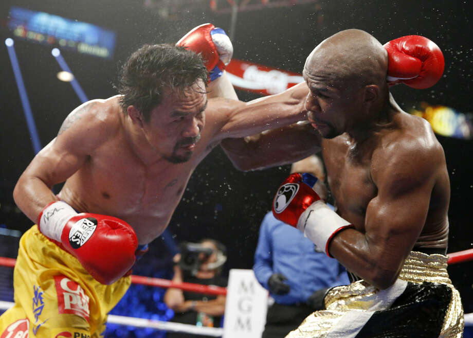 """FILE - In this May 2, 2015 file photo, Manny Pacquiao, left, from the Philippines, trades blows with Floyd Mayweather Jr., during their welterweight title fight in Las Vegas. Pacquiao lost his biggest fight in the ring, but that won't stop him from plotting a bigger comeback - in the political arena that is. Some fans still want a rematch because they felt cheated by the lackluster Pacquiao-Mayweather bout billed by promoters as the """"Battle for Greatness,"""" though boxing analyst Ed Tolentino calls it the """"Fiasco of the Century."""" (AP Photo/John Locher, File) Photo: John Locher"""