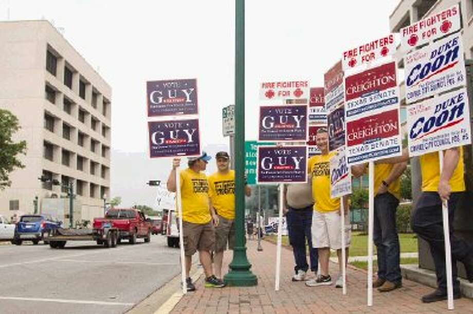 Firefighters hold signs along West Phillips Street during Election Day for the Senate District 4 and municipal positions in Conroe Saturday. Photo: Staff Photo By Ana Ramirez / The Conroe Courier